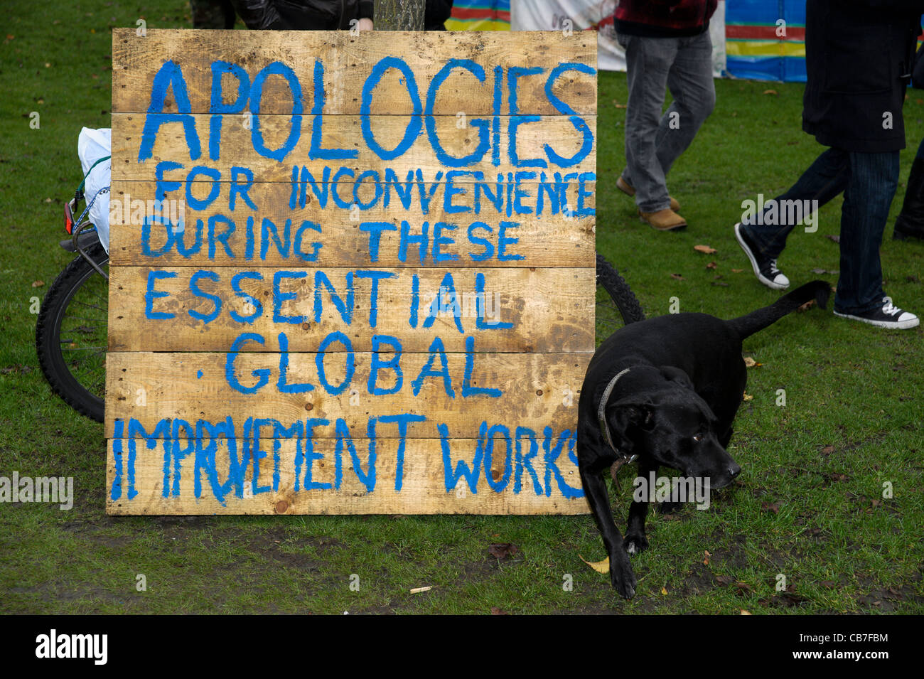 A dog sprays a sign at the Occupy Brighton camp on Victoria Gardens in Brighton - Stock Image
