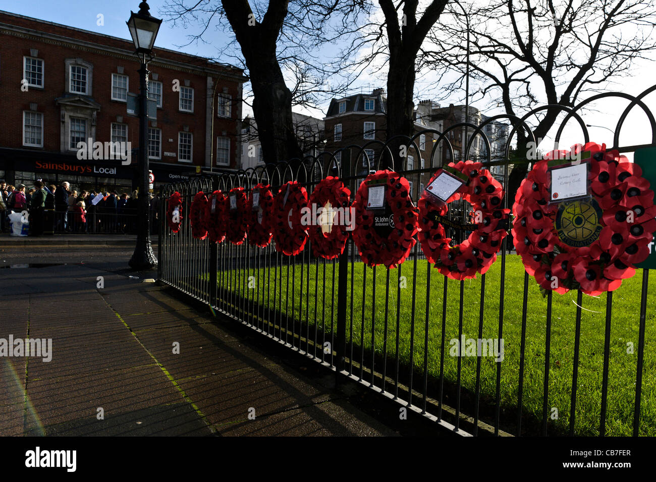 Poppy wreaths hang on a fence in Brighton after a rainfall - Stock Image