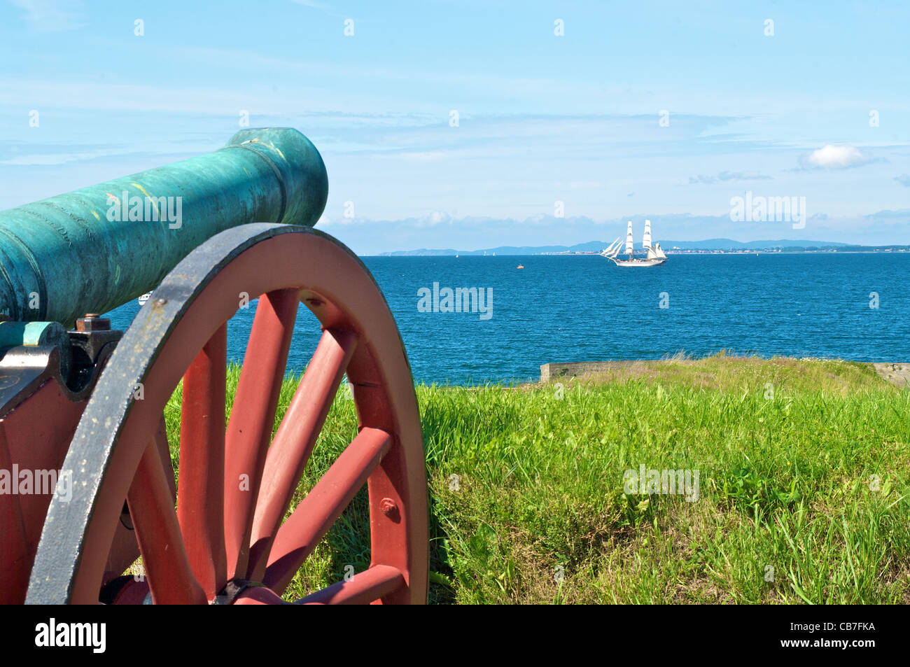 Prehistoric cannon pointing at white ship on the ocean at Kronborg Castle, Elsinore, Denmark - Stock Image