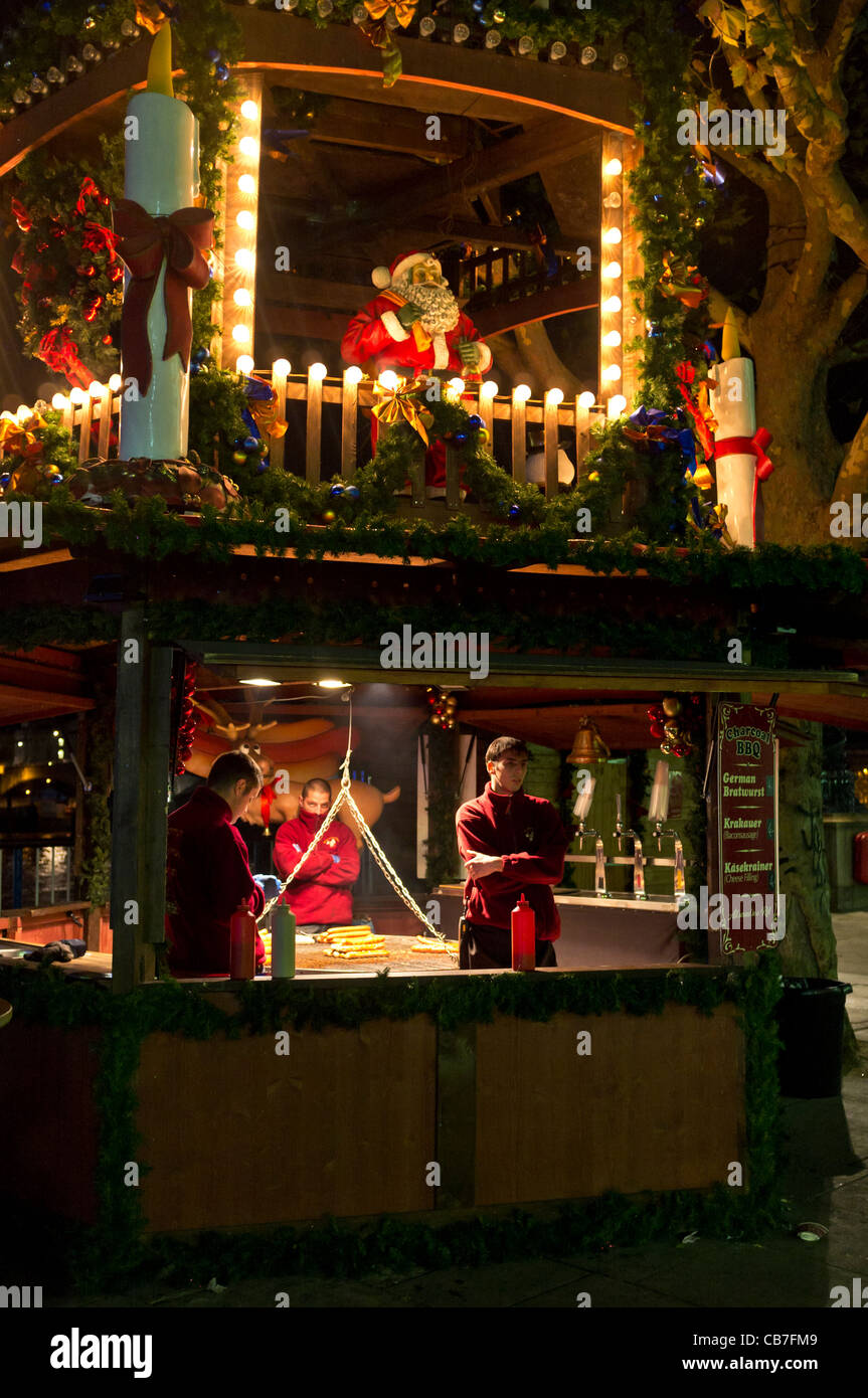 Male staff on a BBQ stall at a Christmas Market wait for custom. - Stock Image