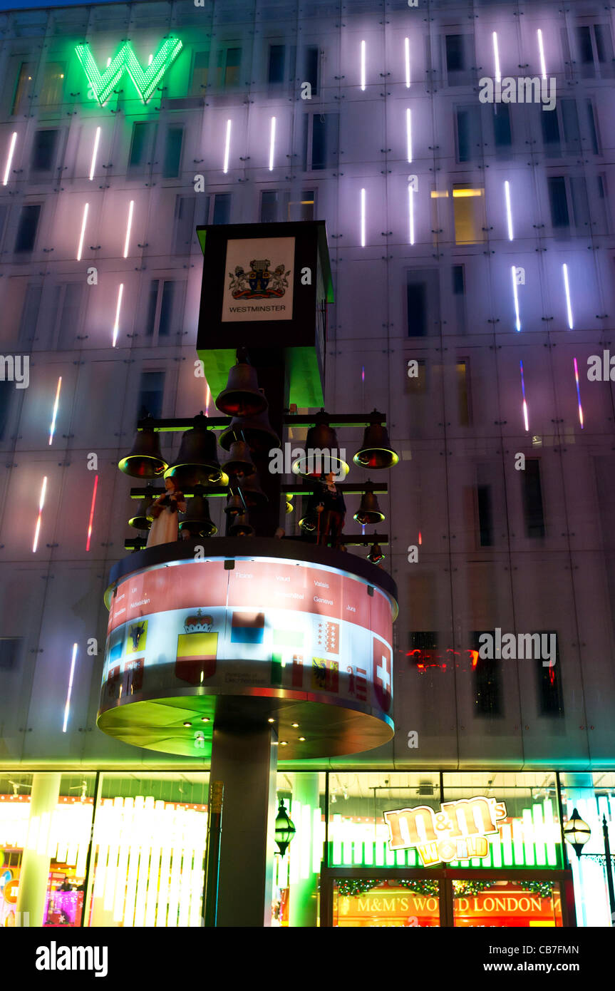 The relocated 'Swiss Clock' outside the W hotel in Leicester Square at night. - Stock Image
