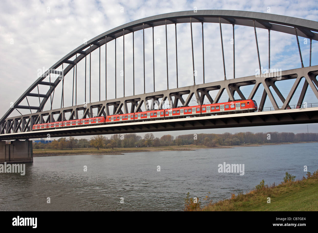 Railway bridge with a Rhine-Ruhr S-Bahn (suburban passenger train) crossing river Rhine, Dusseldorf, Germany. Stock Photo