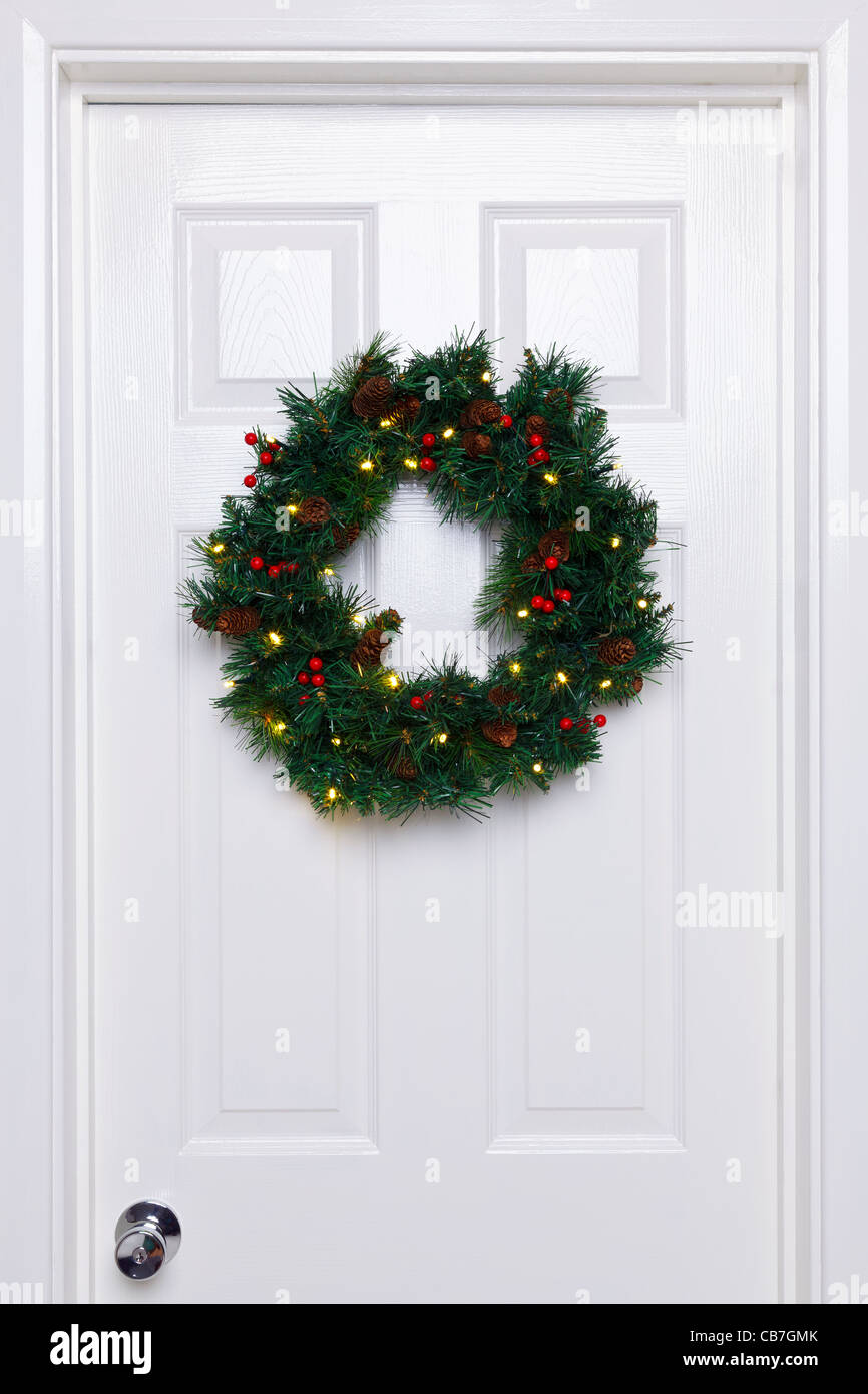 Photo of a Christmas wreath with lights hanging on a white front door. Stock Photo