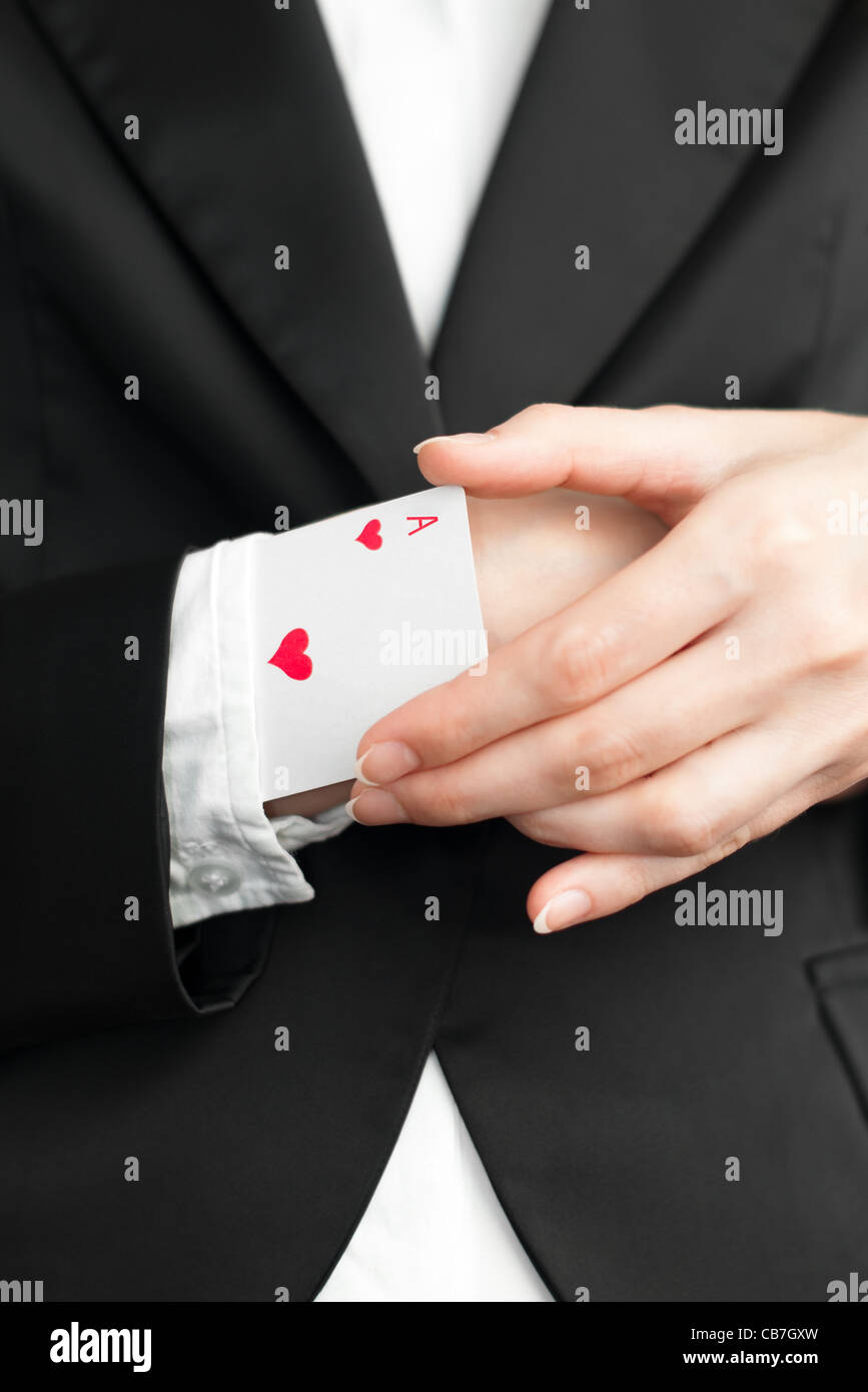 young businesswoman pulling out ace of hearts from the sleeve of her suit - Stock Image