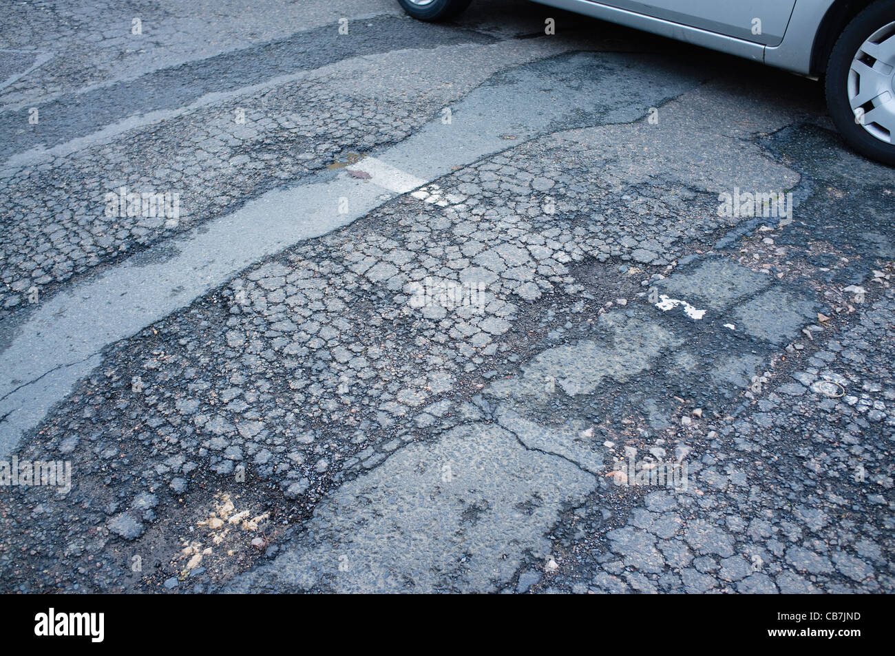 A  road which is worse for wear and in need of repair  with potholes and broken tarmac. UK - Stock Image