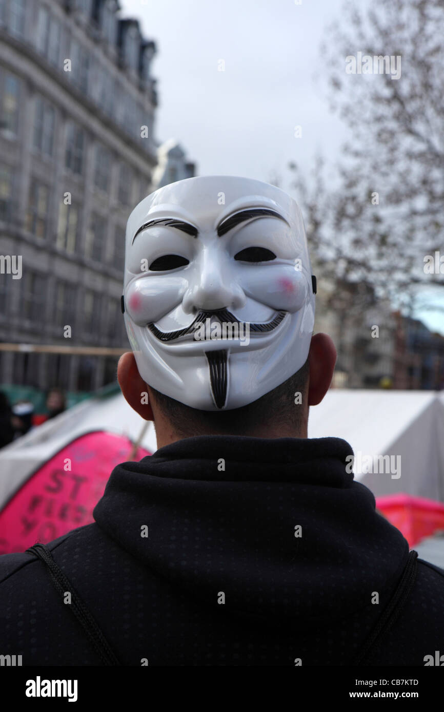 back of man with Guy Fawkes Mask, symbol of Anonymous movement anarchist hacktivist group, Occupy London, St Paul's - Stock Image