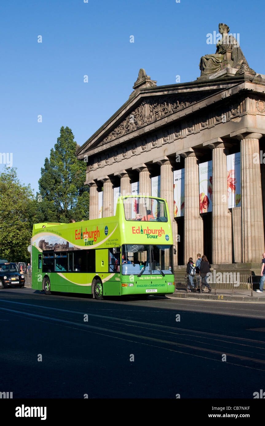 An open top double deck tour bus passes the Royal Scottish Academy Building in Princes Street, Edinburgh. - Stock Image