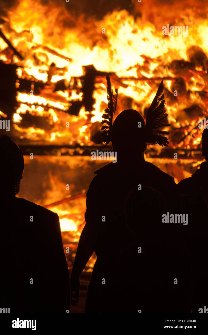 Silhouetted 'Vikings' against a burning Viking Galley at the Up Helly Aa festival in Lerwick on the Shetland Islands. Stock Photo