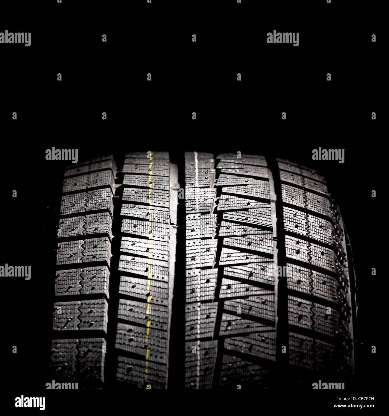 Part of brand new car tyre isolated on a black background. Square format. - Stock Image