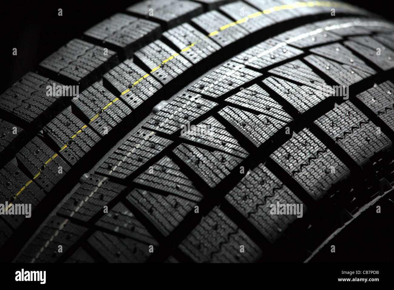 Part of brand new car tyre. Shallow DOF. Black back background. - Stock Image