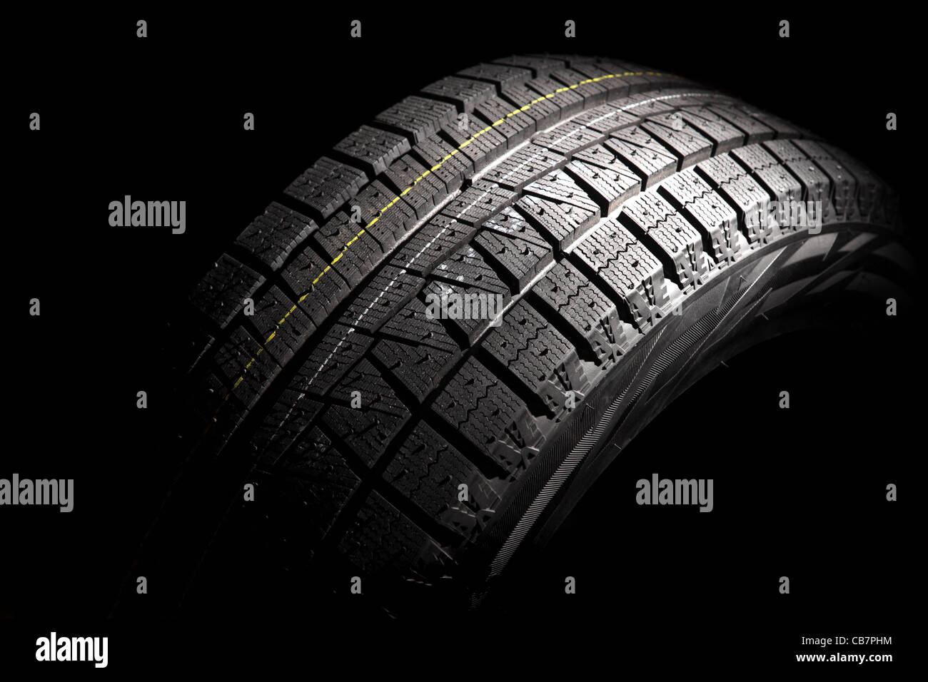 Modern winter car tyre. Horizontal composition. Low key. - Stock Image