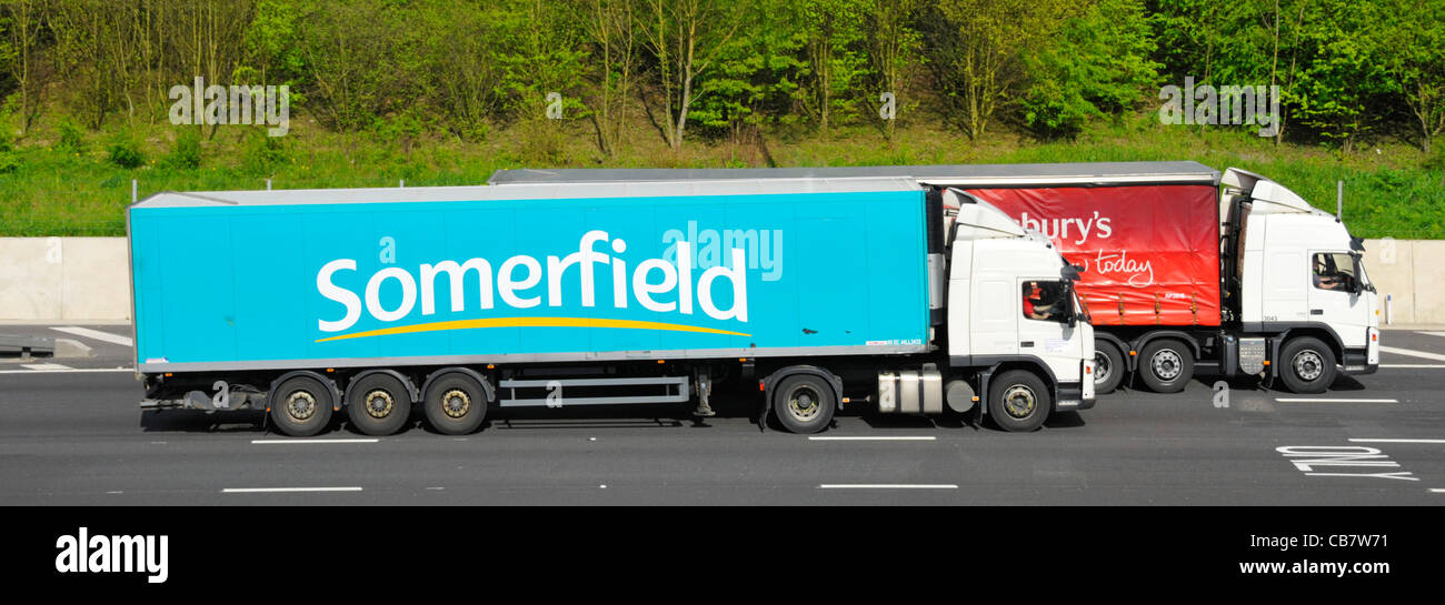 Supermarket food supply chain Somerfield articulated trailer & hgv lorry overtaking Sainsburys articulated trailer Stock Photo