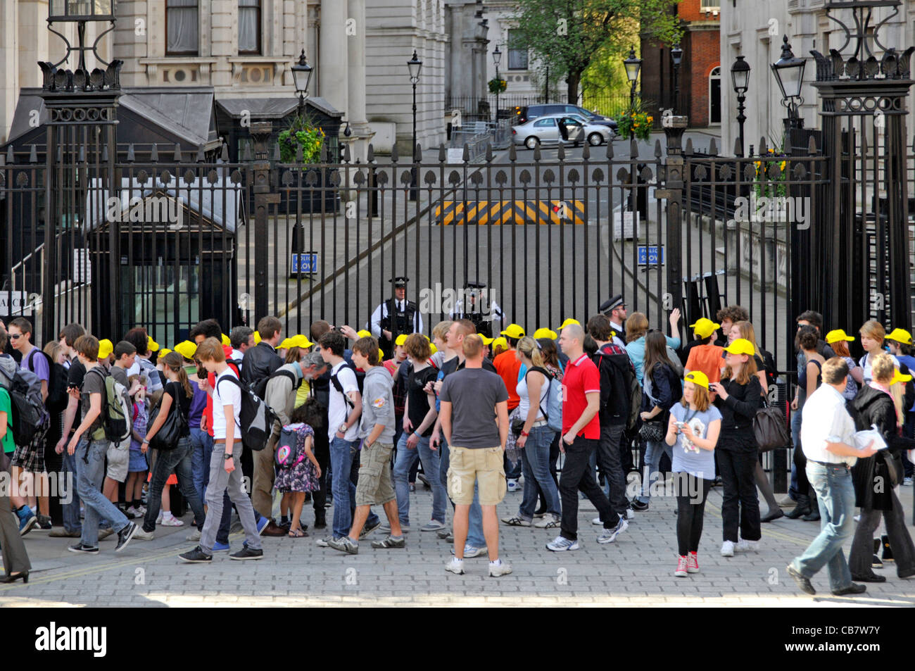 Armed London Metropolitan police officers behind security gate protect access to10 Downing Street tourists & group Stock Photo