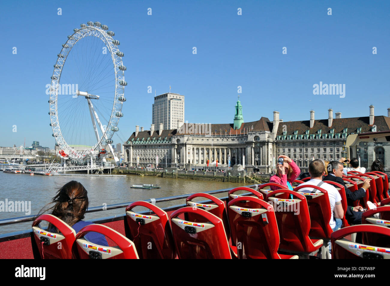 Tourists on open top sightseeing bus crossing Westminster Bridge with views of River Thames and the London Eye - Stock Image
