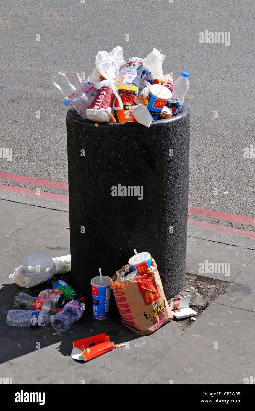 Waste management required to overflowing roadside litter bin full with rubbish garbage litter & trash spilling - Stock Image