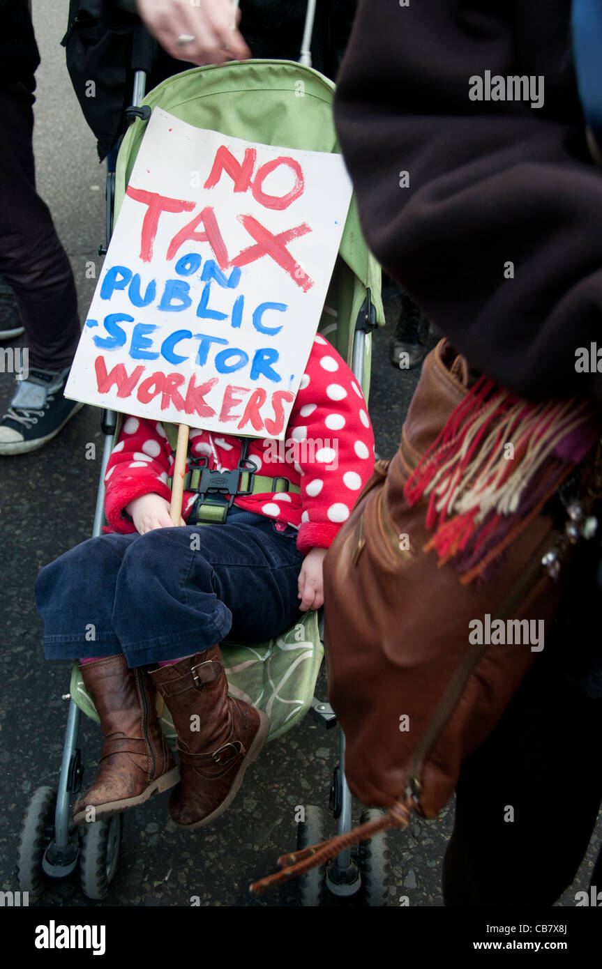 One day strike against pension cuts . Child sleeps in a pushchair with placard says No tax on public sector workers. - Stock Image