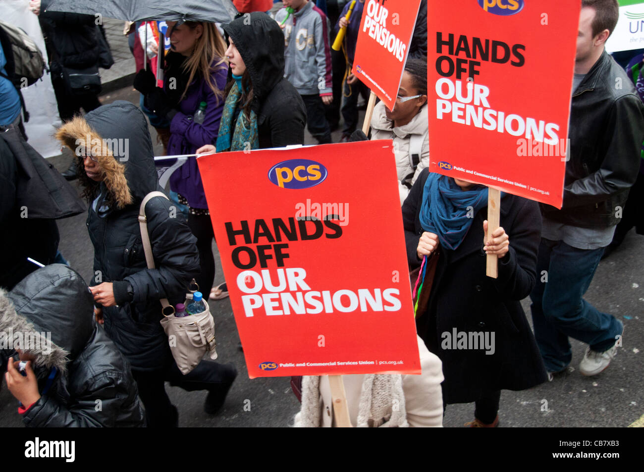 One day strike against pension cuts by public sector workers.PCS union members march in the demonstration with flags. - Stock Image