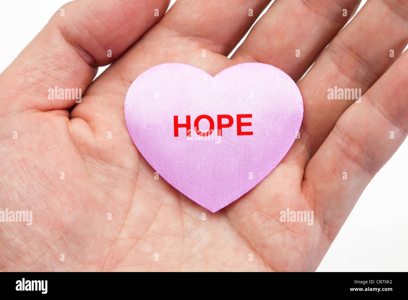 hand holding a Pink heart, concept of hope - Stock Image