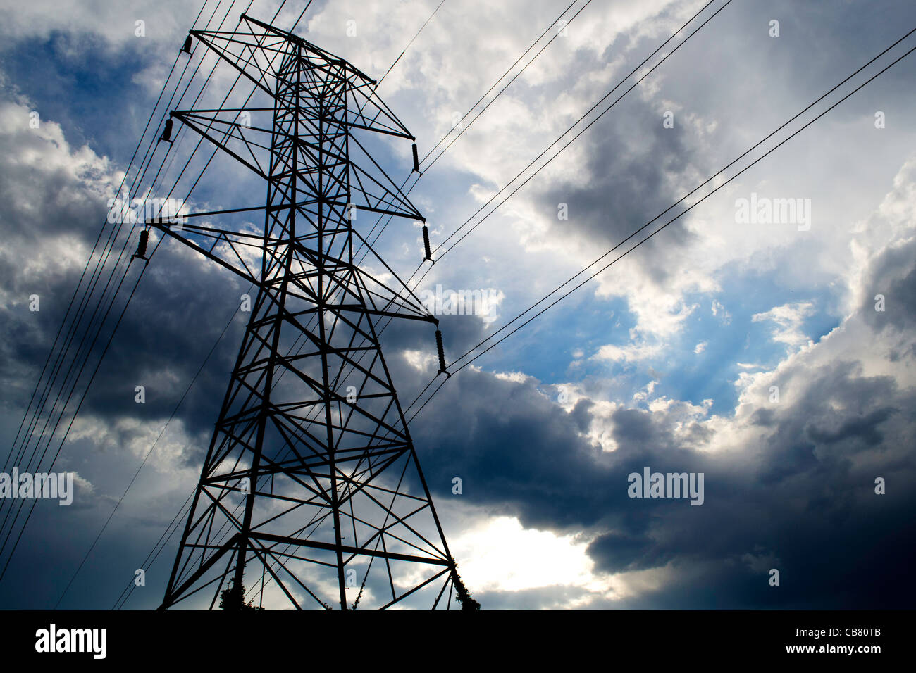 A huge electrical tower stands against a dramatic sky-- the shadow of the grid, Vermont USA - Stock Image