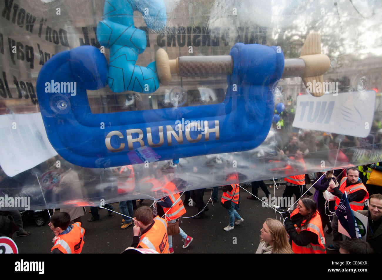 One day strike against pension cuts by public sector workers.  A giant inflatable with a £ sign being squeezed - Stock Image