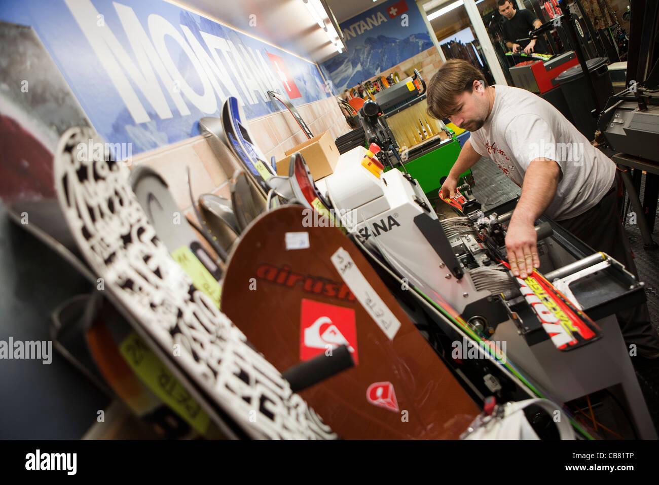 Ski rental service in Prague on November 23, 2011. Service man waxes ski. (CTK Photo/Martin Sterba) - Stock Image