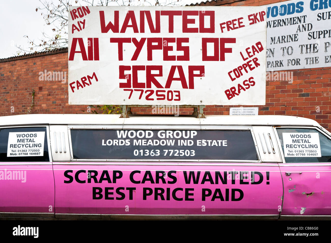 Scrap dealer with sign saying 'scrap cars wanted' on side of pink Cadillac - Stock Image