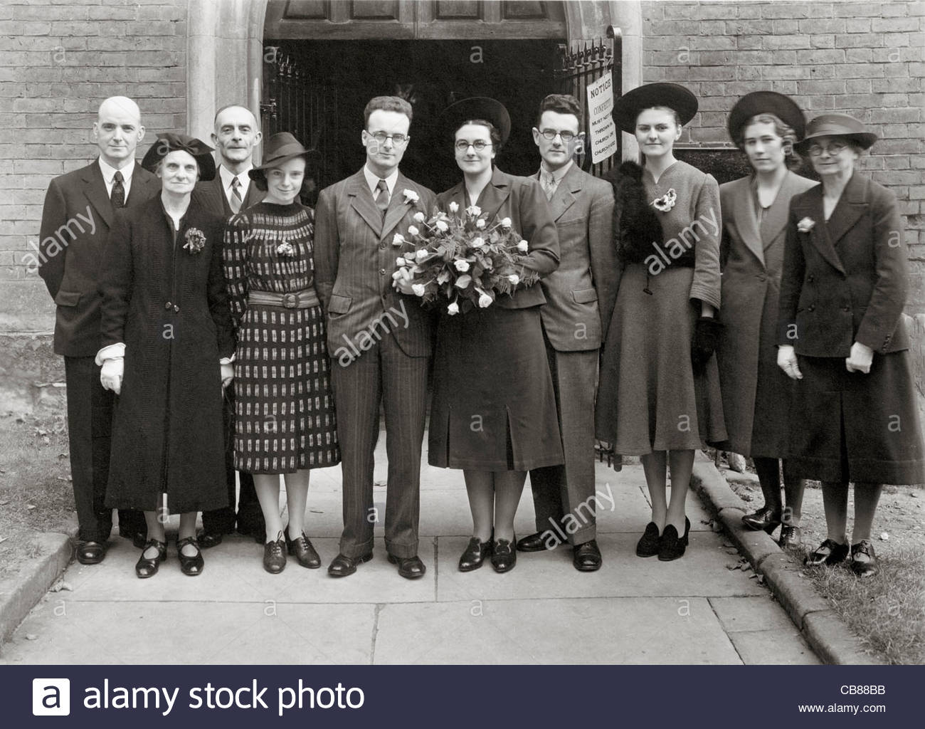 group family wedding photo in front of the church door opening England 1940s - Stock Image