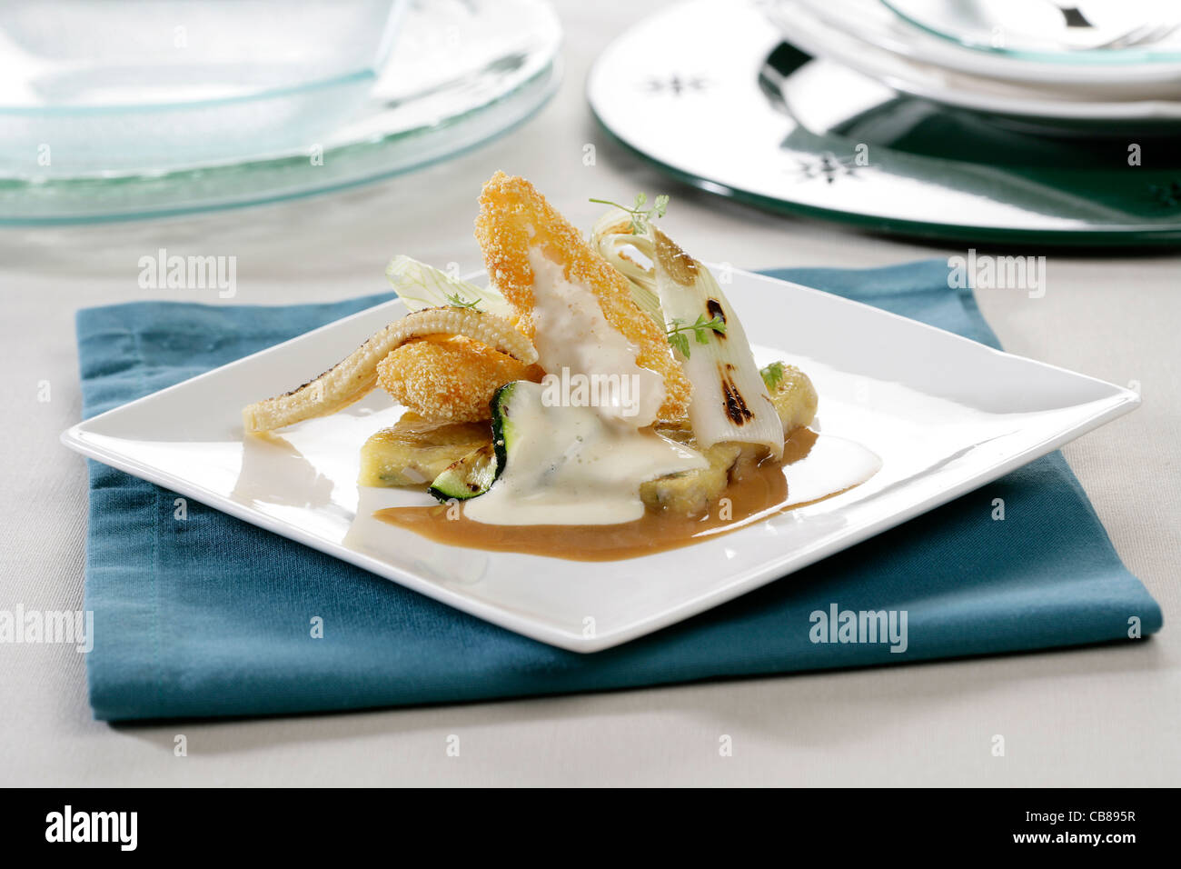 Breaded Scampi over polenta with vegetables and seafood and cheese juice Stock Photo