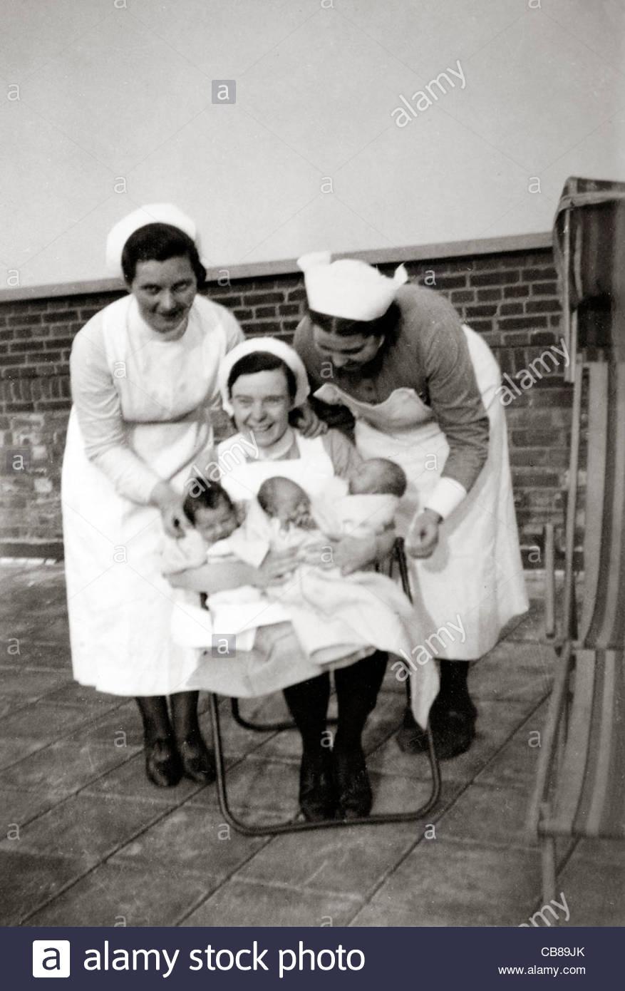 three nurses posing with newborn babies England 1930s - Stock Image