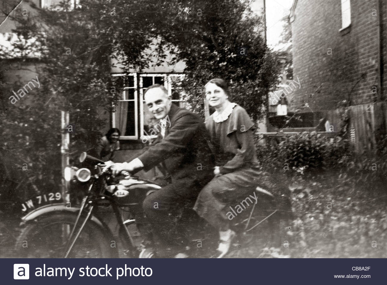 elderly couple in front of a house sitting on a motorcycle - Stock Image