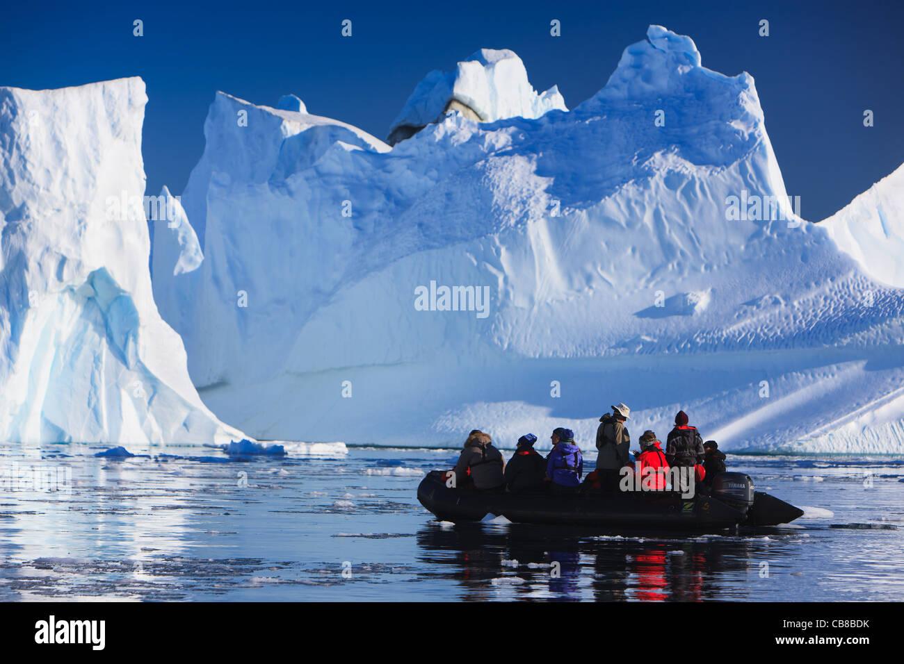 Zodiac cruising between the icebergs at Røde Ø, Scoresbysund, Greenland - Stock Image