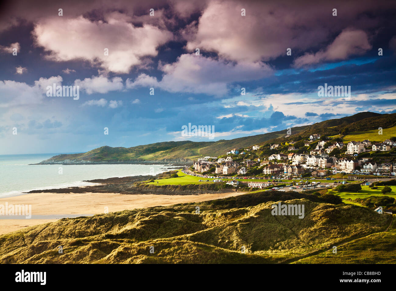 Evening light falls on the English coastal resort town of Woolacombe in Devon, England, UK with Morte Point in the - Stock Image