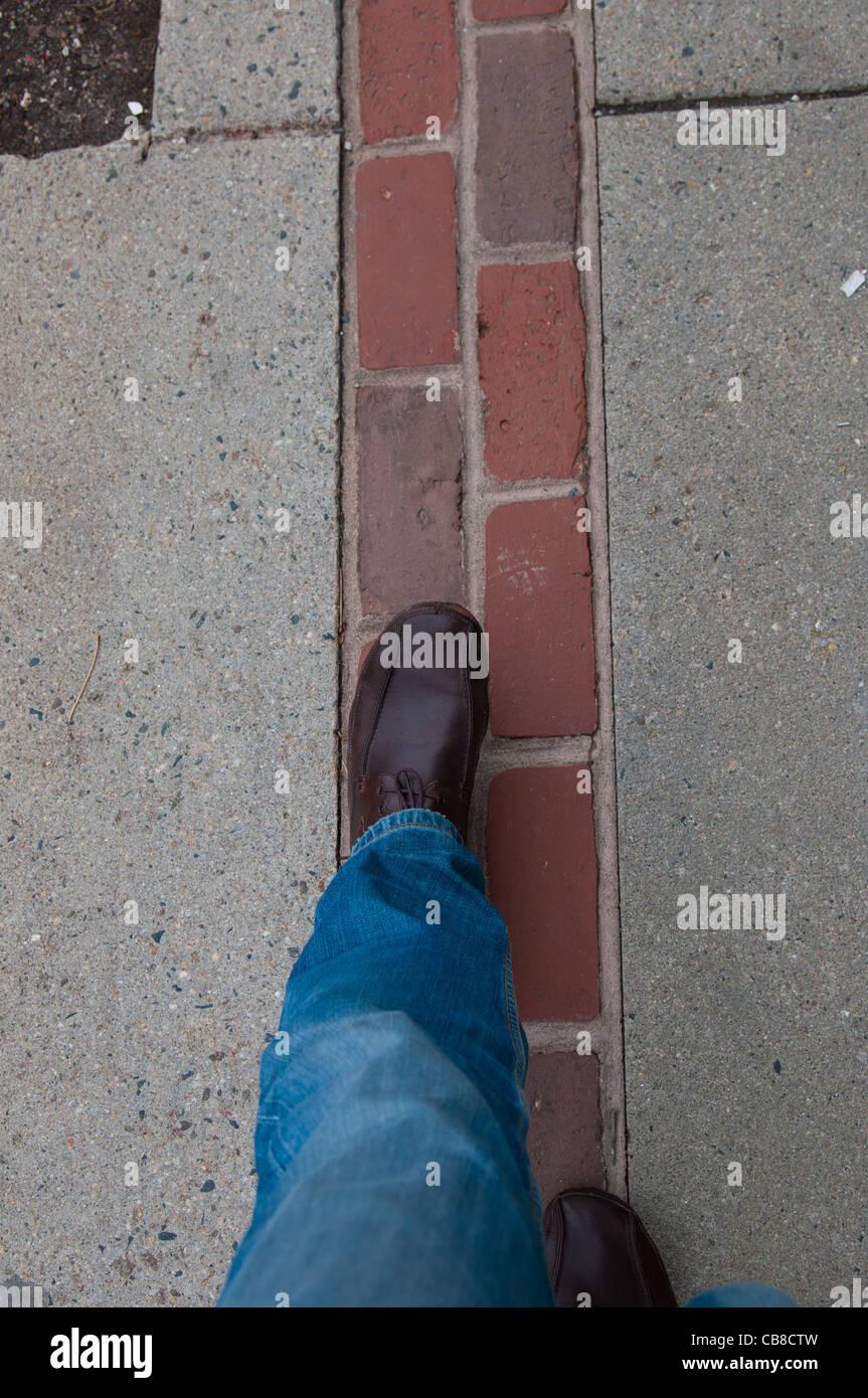 Legs walking down the Freedom trail red bricks in Boston, MA - Stock Image