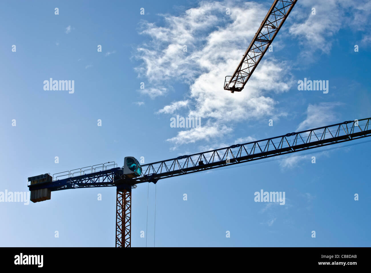 Silhouettes of construction cranes against a blue sky - Stock Image