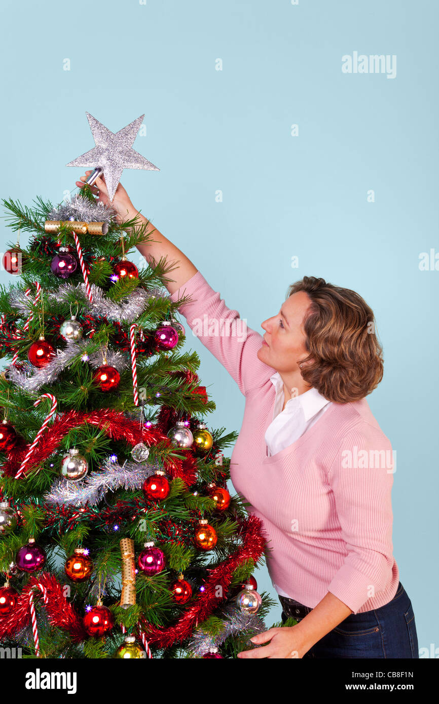 At Home Christmas Trees.Photo Of A Woman At Home Decorating Her Christmas Tree And