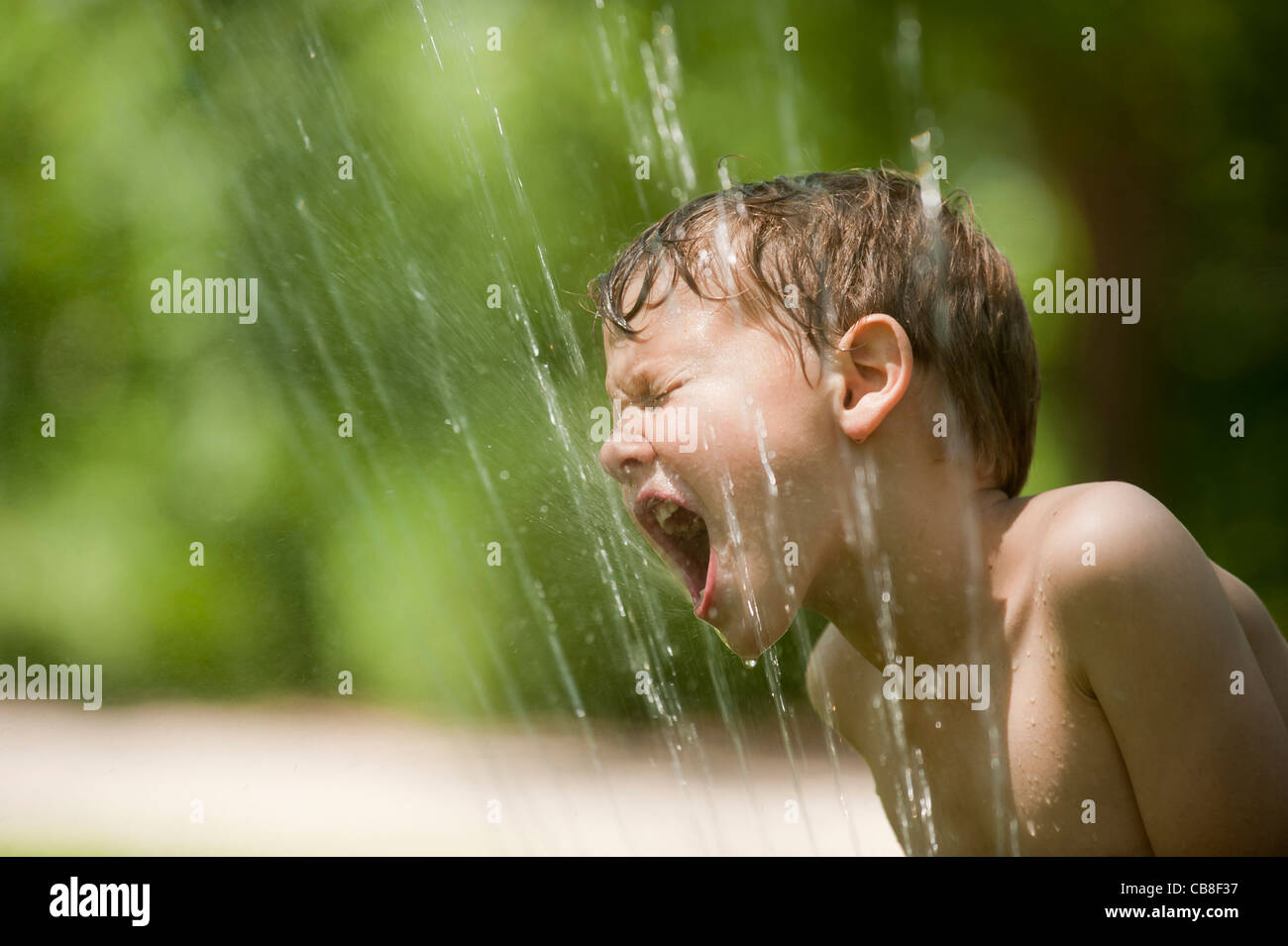 A boy tries to take a drink from a water sprinkler. - Stock Image