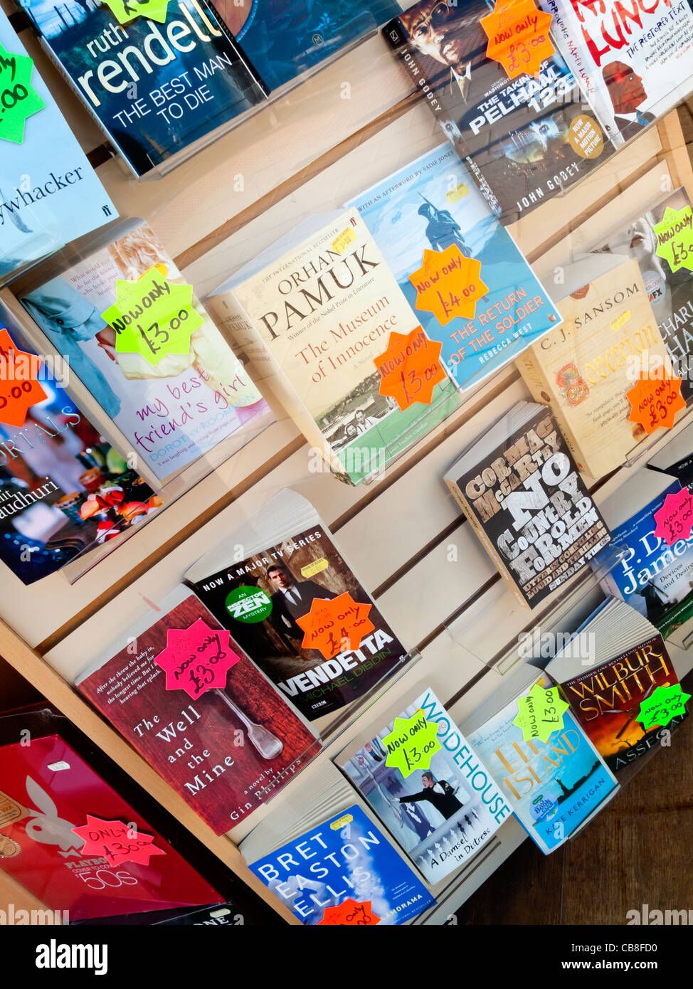 Mass market paperback books for sale in the shop window of a discount bookseller in the UK - Stock Image