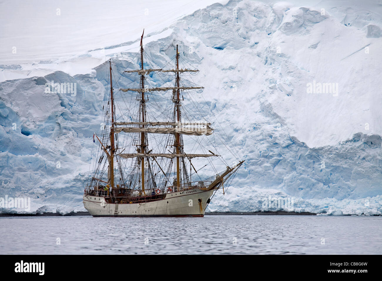 The tallship / three-master Europa, a three-masted barque in front of a giant glacier wall in Antarctica - Stock Image