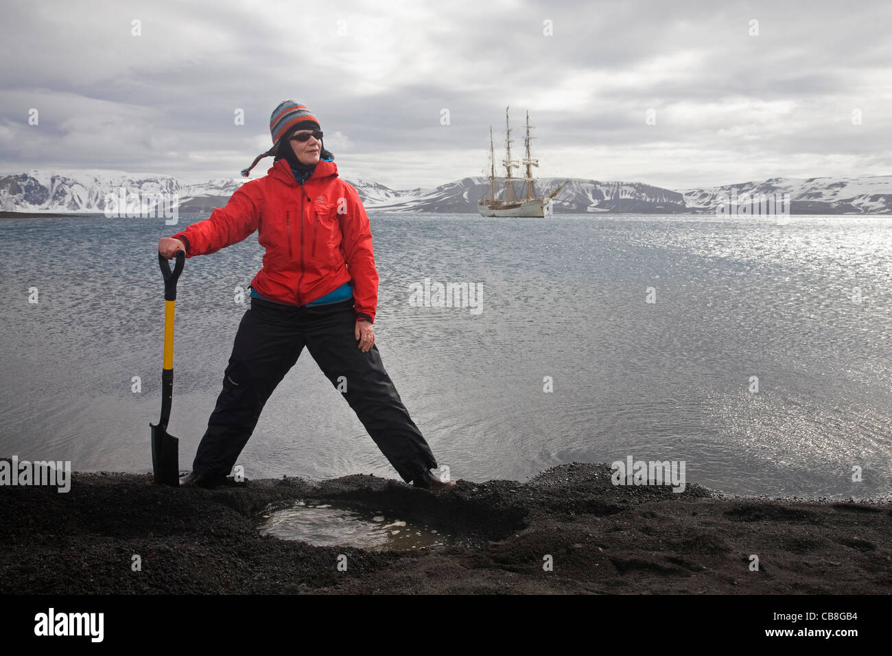 Tourist digging hot tub with volcanically heated water at Pendulum Cove, Deception Island, South Shetland Island, - Stock Image