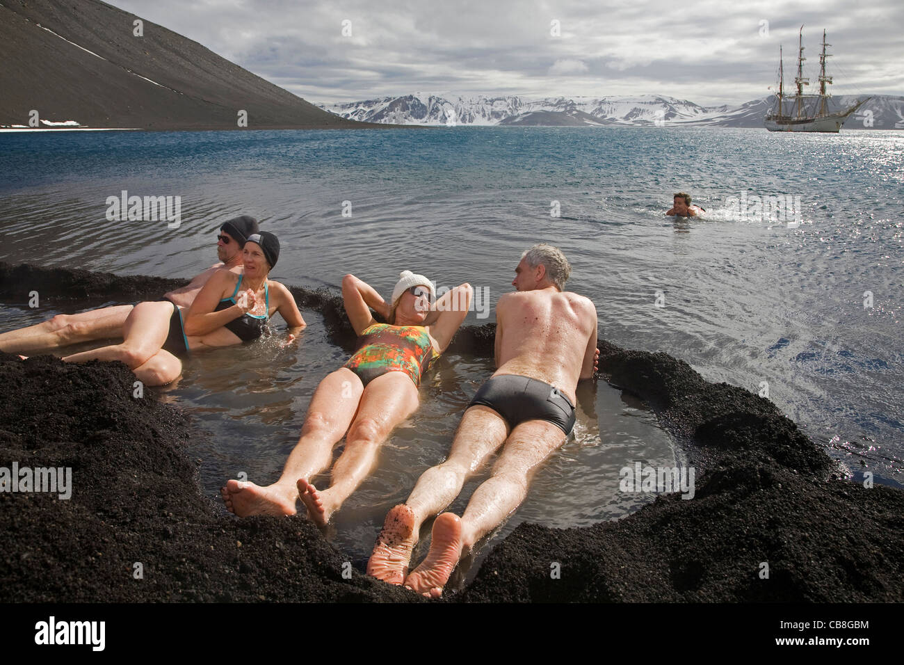Tourists bathing in hot tub with volcanically heated water, Pendulum Cove, Deception Island, South Shetland Islands, - Stock Image
