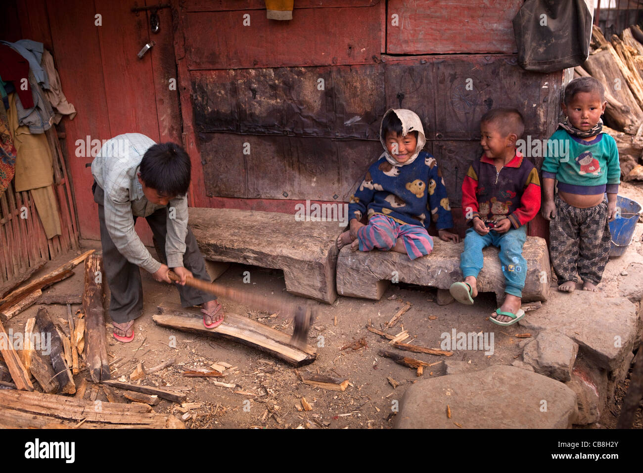 India, Nagaland, Jakhama Village, child chopping firewood with axe close to other young children - Stock Image