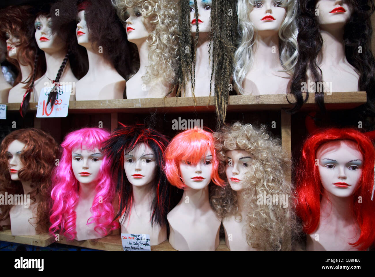 Female wigs on mannequin heads. - Stock Image