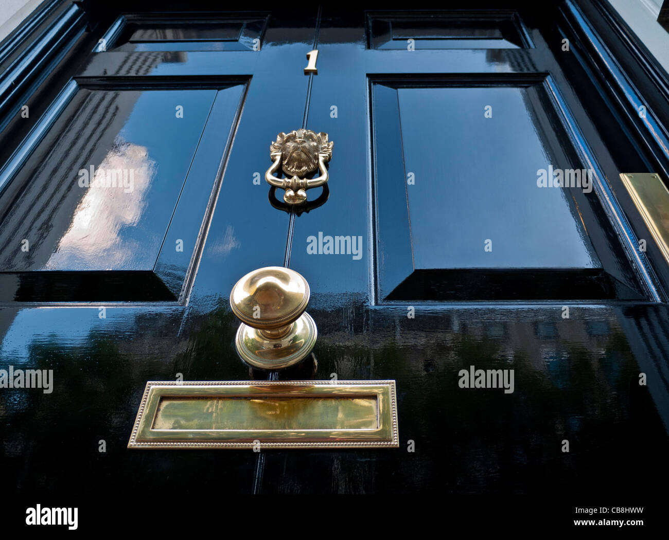 An imposing black paneled Georgian front door 'Number 1' with traditional brass fittings London England - Stock Image