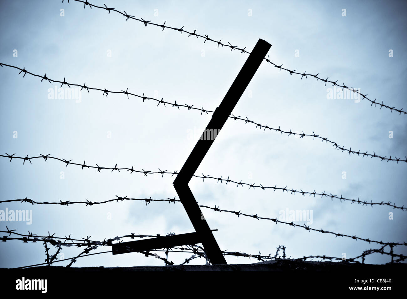 photo of old rusty barbed wire against sky Stock Photo