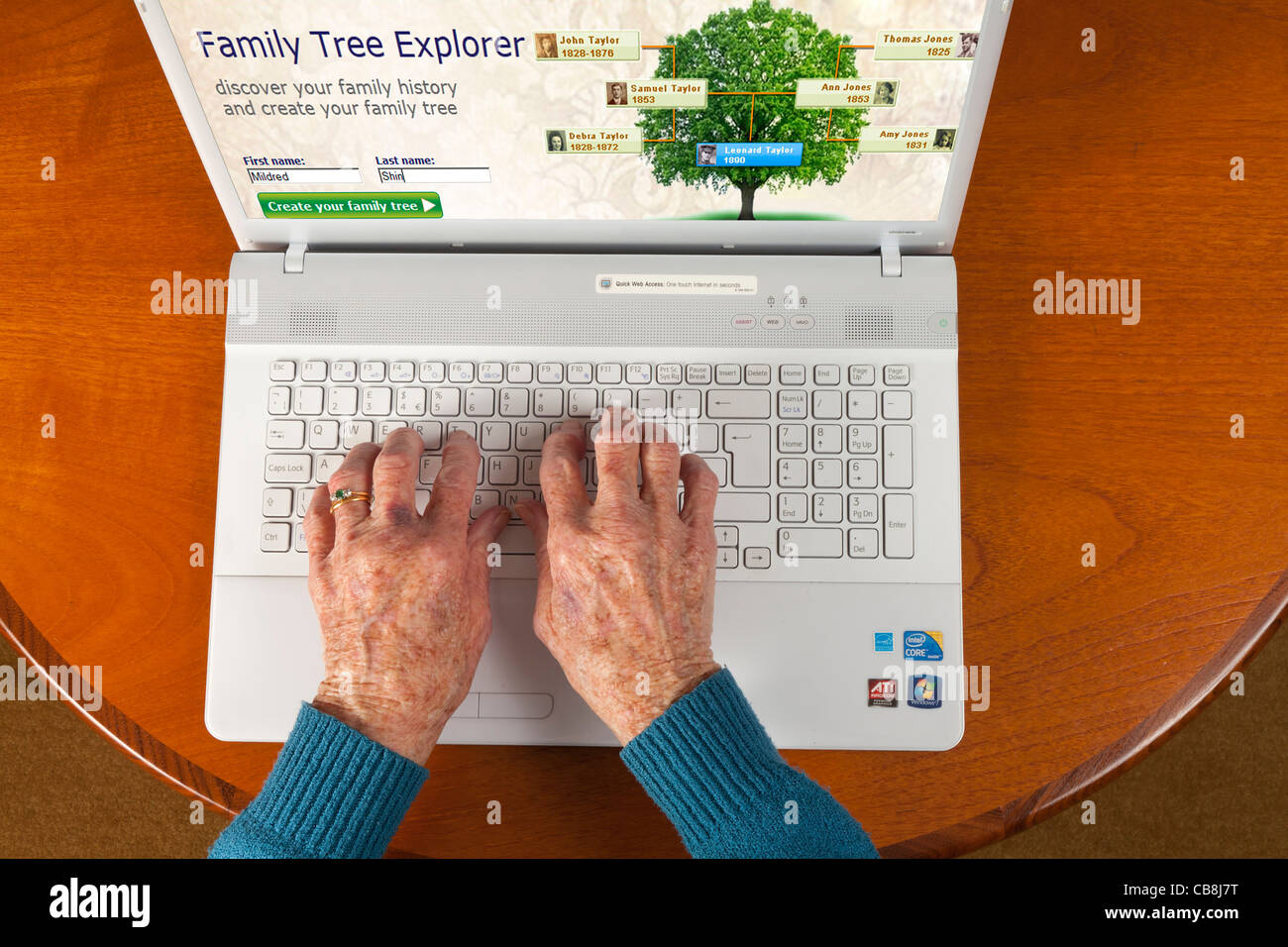 Female elderly hand using a laptop to check the family tree via the internet - Stock Image