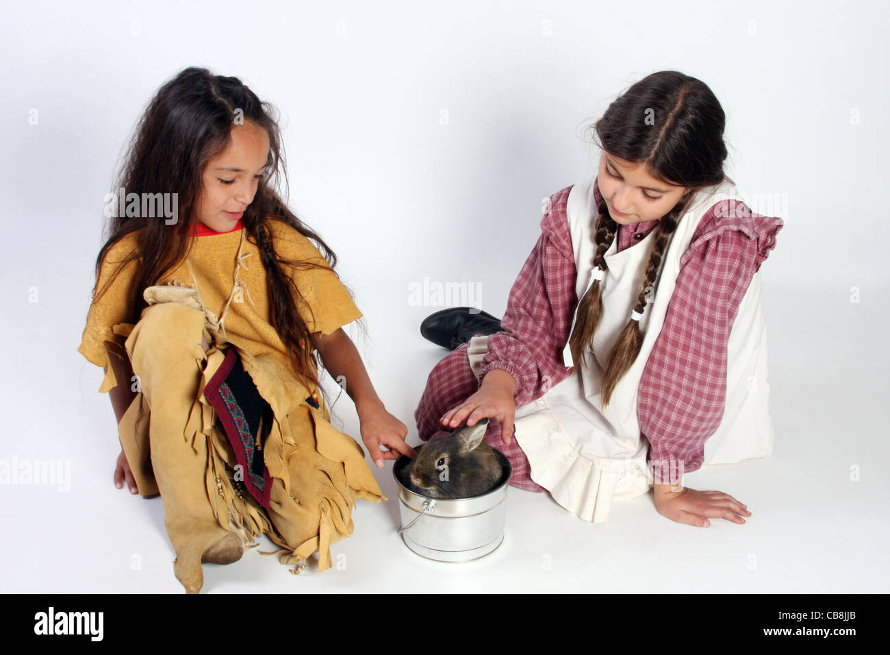 A young Native American Indian child and a settler girl petting a bunny  rabbit - Stock