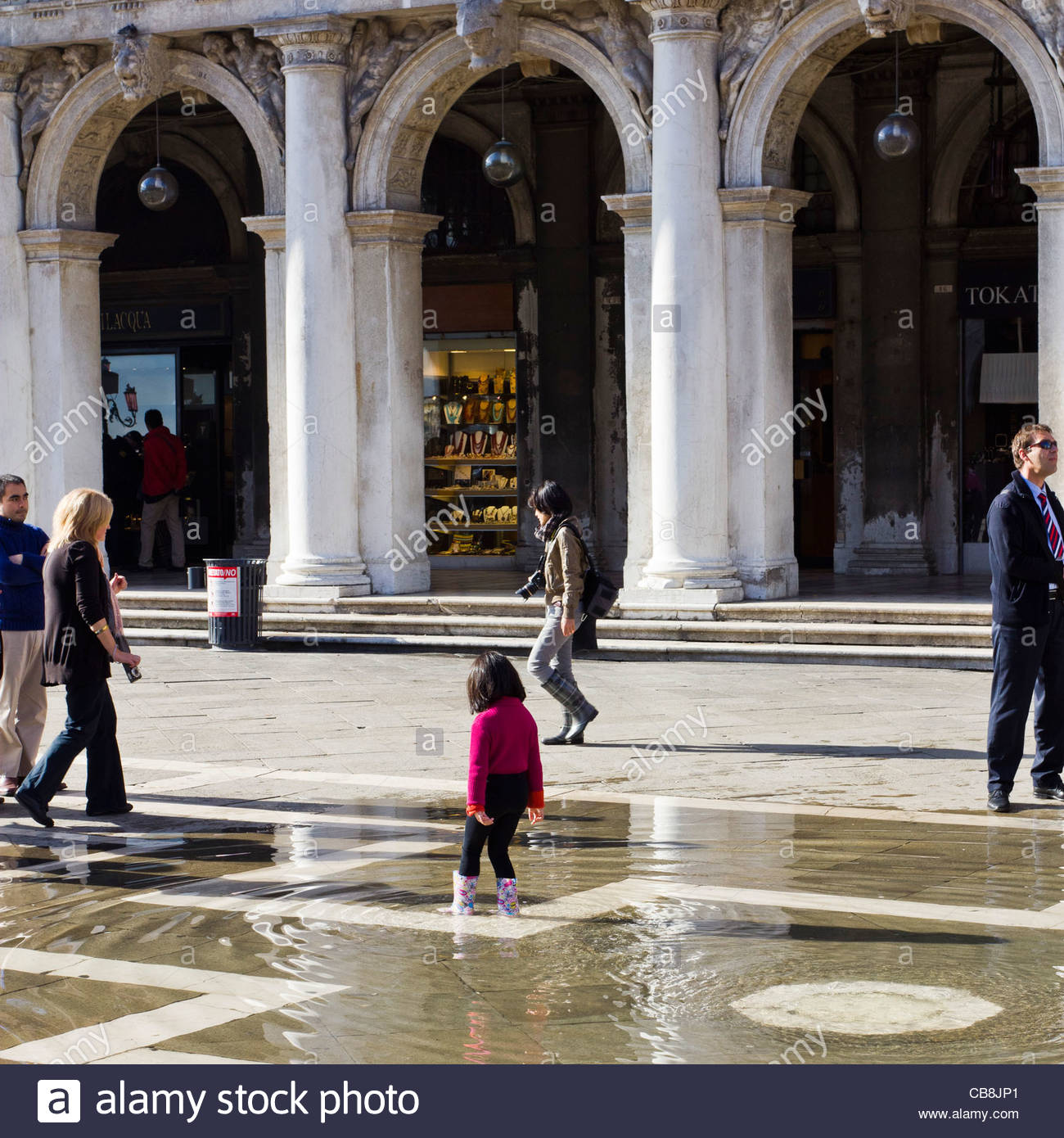 Venice Italy. Young girl plays in floodwater bubbling up from rain runoff drains. Stock Photo