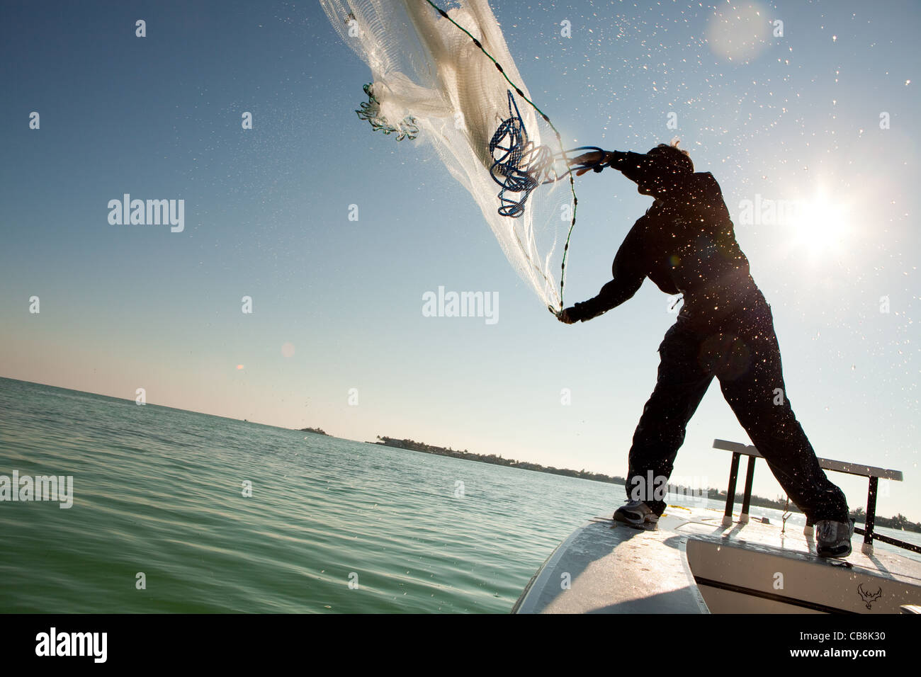 Fisherman casting a net off his boat in the Florida Keys. Stock Photo