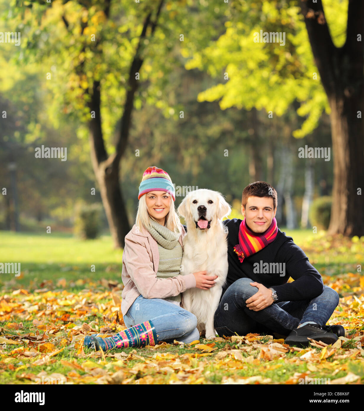 Smiling young man and woman hugging a dog out in the park - Stock Image