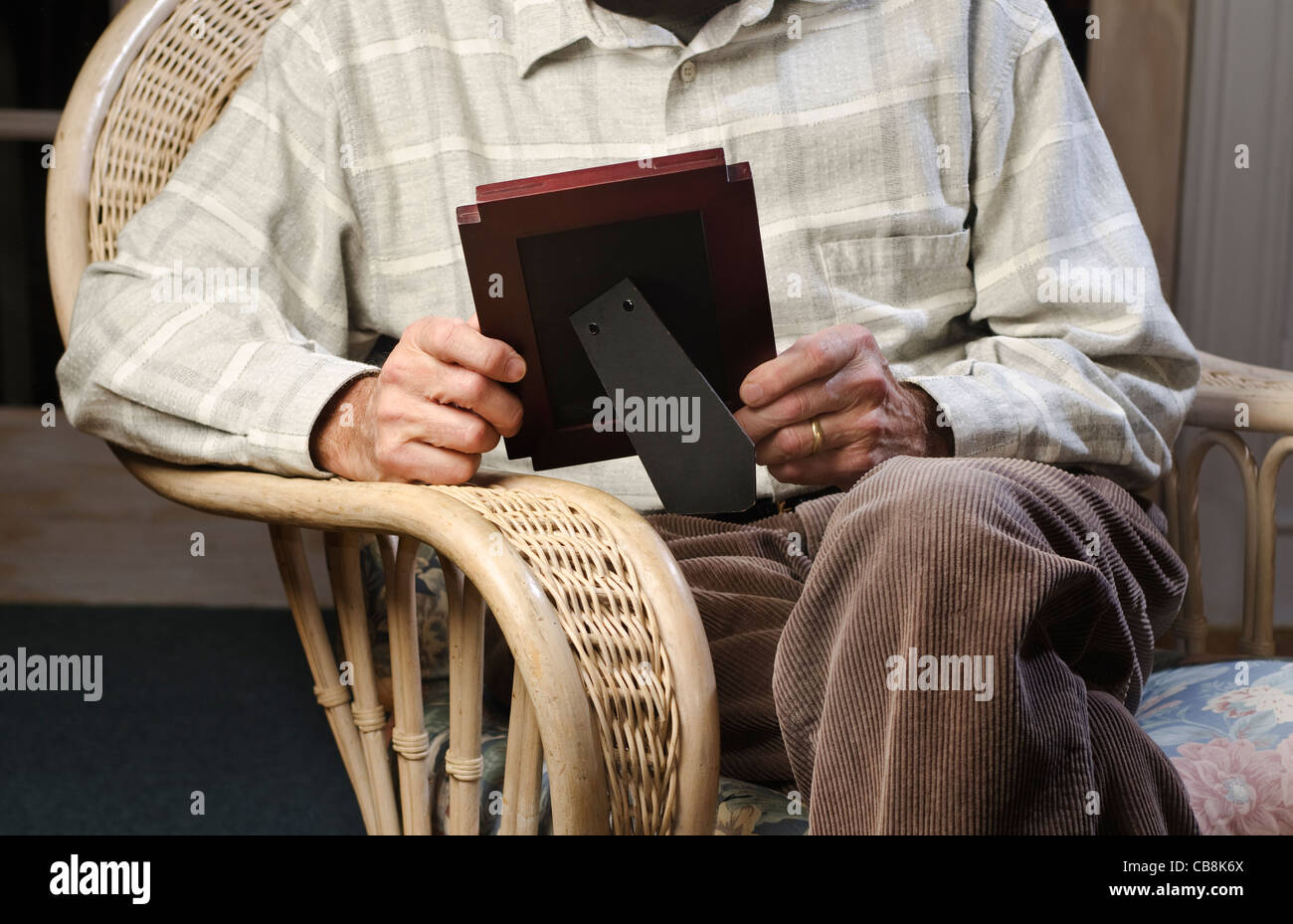 man seated on easy chair looking at picture frame - Stock Image
